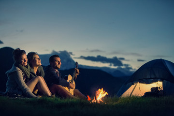 Wall Murals Camping Three friends camping with fire on mountain at sunset