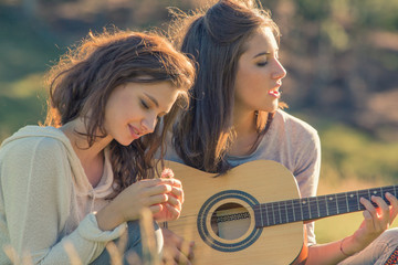 Young woman sing playing guitar with friend on sunset outdoor