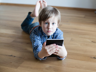 cute boy lying on the wooden floor and reading electronic book