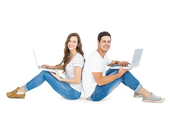 Happy couple sitting on the floor back to back using laptop