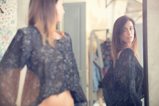 Young woman looking in the mirror portrait in a shop