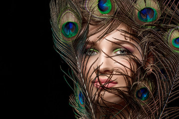 girl with bright  makeup and peacock feathe