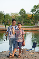 Excited Vietnamese boy and his father showing fish they caught