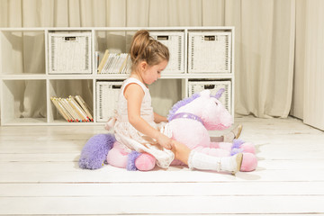Cute little girl riding on a pink pony toy. Children imagination or creativity concept. Princess...