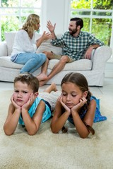 Upset children lying against parents fighting at home