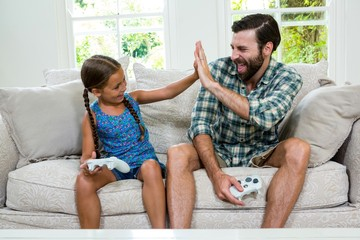 Father and daughter doing high five while sitting on sofa