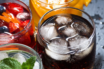 assortment of fresh iced fruit drinks on a dark background
