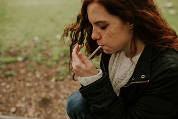 Redhead teen woman smoking in the forest