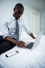Young man sitting on bed and using laptop