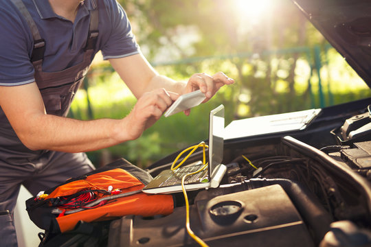 Professional car mechanic working in auto repair service, photog