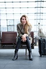 Junge Geschäftsfrau am Bahnhof auf einer Bank