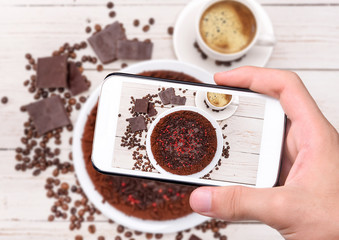 Hands taking photo truffle chocolate cake with smartphone.
