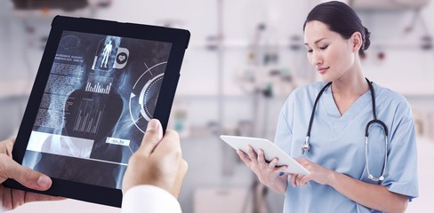 Composite image of surgeon using digital tablet with group