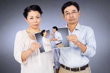 Composite image of asian couple holding a photo