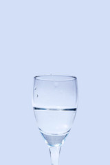 Close up water in wine glass on blue background