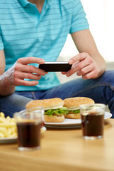 close up of man with smartphone picturing food