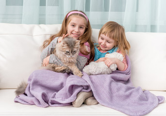 two lovely little girls embracing on sofa