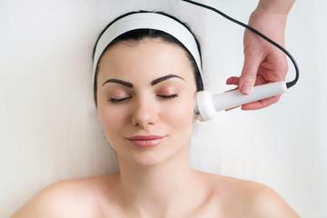Schöne junge Frau macht Ultraschall Hautreinigung und Gesichtsbehandlung bei Kosmetikerin im Schönheitssalon
