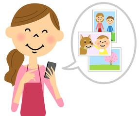 スマートフォンを触るエプロンの女性