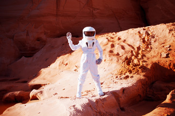 Futuristic astronaut  on  sandy planet, waving at the camera. Image with effect of toning