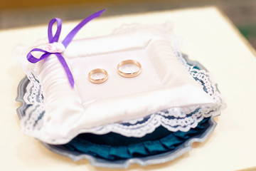 gold wedding rings on a white pillow