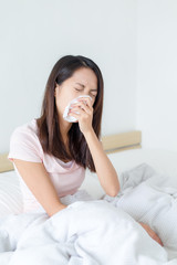 Woman suffer from sick and sneeze on bed