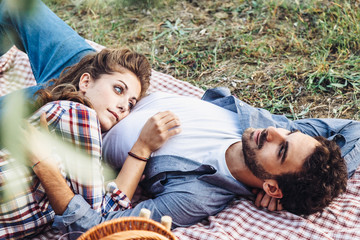 On a late summer day, a pair of young lovers is lying on the grass. The head of the young woman's belly on him. Picture taken in a field in Tuscany, Italy