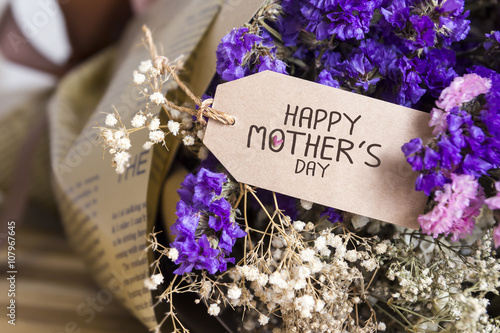 Bouquet of dried flowers with mothers day card on the wooden tab