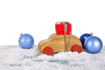 Wooden toy car with gift box and baubles on a snowy table over white background