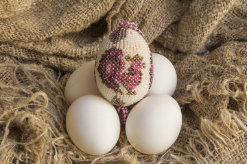 souvenir beaded egg on white raw eggs