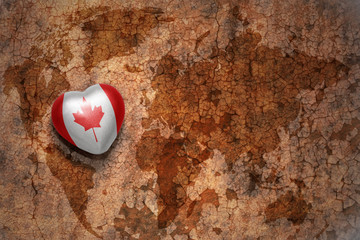 heart with national flag of canada on a vintage world map crack paper background. concept
