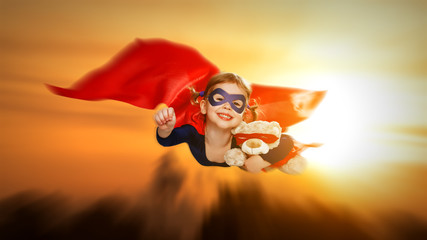 child girl superhero with teddy bear flying through sky at sunse