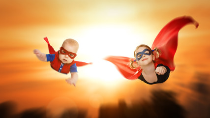 children superheroes flying across sunset sky