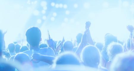 Ein Konzert, Menschen feiern, haben Spaß an der tollen Musik, sie klatschen Beifall und sie tanzen fröhlich