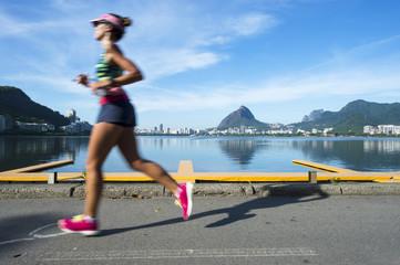 A jogger running past in motion blur a calm morning view of Lagao Rodrigo de Freitas lagoon, a popular recreation destination in Rio de Janeiro, Brazil