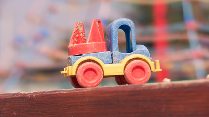A detail of a color plastic truck toy during lovely spring time on the playground for kids - color toned image - focus on cabin
