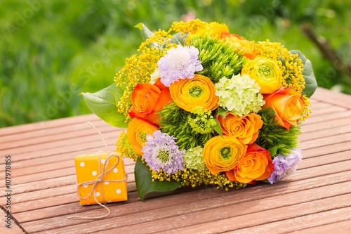 wundersch ner blumenstrau mit rosen und ranunkeln und kleines geschenk auf gartentisch. Black Bedroom Furniture Sets. Home Design Ideas