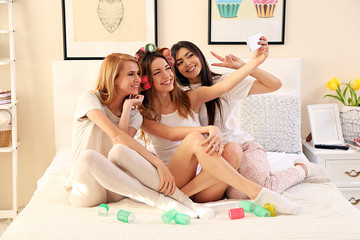 Three girls taking photo by their self with mobile phone on a bed in living room
