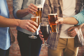 Male group clinking glasses of dark and light beer on brick wall background