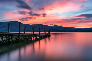 Beautiful pink and purple vibrant sunset with a jetty at Derwentwater, Keswick, Lake District, UK.