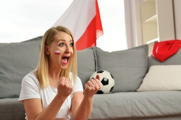Polish fan cheers football team in the national colors.
