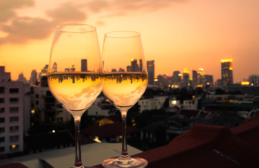Wall Mural - Night view of the city reflected In pair of wine glasses.
