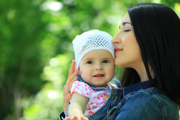 Mother kissing and holding daughter