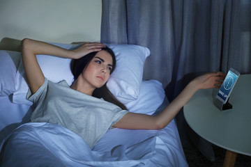 Young woman looking at the mobile phone in bed at night