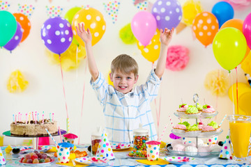 Happy funny little boy at birthday party