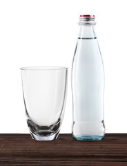 Mineral water in bottle and clean glass on wooden table on grey background