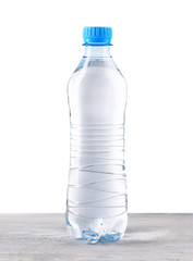 Mineral water in plastic bottle on wooden table on grey background