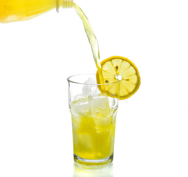 Lemon drink pouring into glass on white