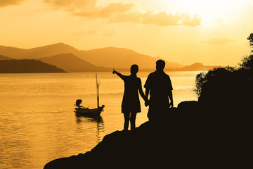 Silhouette of romance couple standing on a rock in sunset