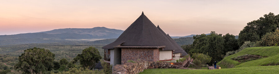 Panoramic view on lodge hotel bungalows against sunrise glowing over mountain background at dawn. Ngorongoro, Great Rift Valley, Tanzania, East Africa.